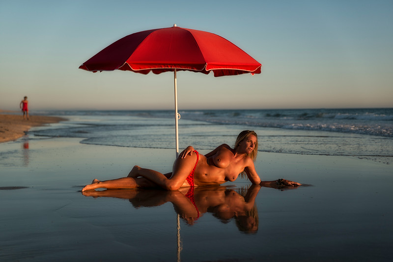 A lady enjoying the sunset at El Palmar beach.<br /> <br /> Vejer, Andalucia, Spain