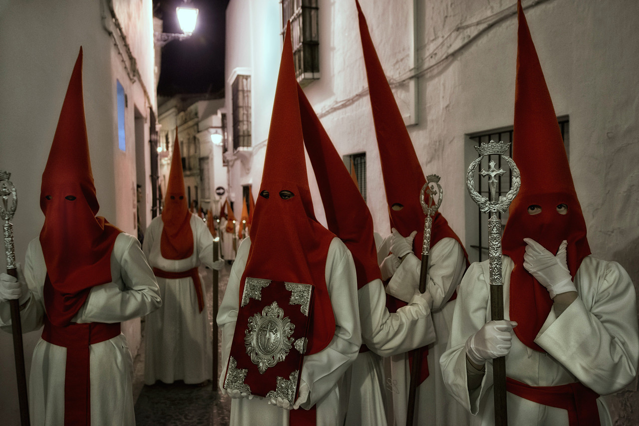 """The pointed hat seen here during Spain's Easter celebrations was worn by clowns and jugglers who wanted to portray clumsiness or stupidity during medieval times. Because of this, pointed hats were used when vexing criminals. The criminals were forced to wear pointed hats and walk through the streets, while people threw rotten vegetables at them, spat on them, and insulted them.<br /> Later, during the celebration of the Holy Week/Easter in Mediterranean countries, """"Penitentes"""" (people doing penitence for their sins) would walk through streets with pointed hats. It was a way of self-injury; however, they covered their faces so they wouldn't be recognized.<br /> The capirote is not to be confused with the pointed hood worn by the member of the Ku Klux Klan, and predates such hoods.<br /> <br /> Arcos de la Frontera, Andalucia, Spain, 2014"""