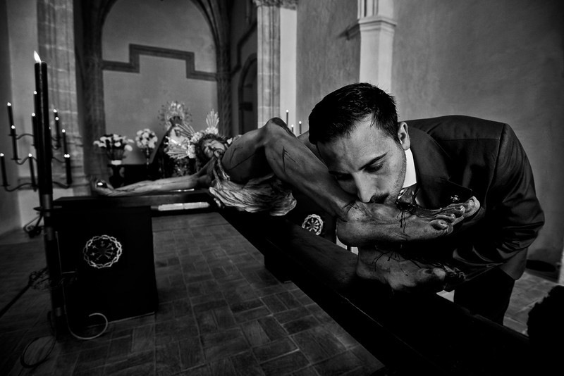 A man kisses the feet of an image of Christ, which will later be taken around town in a procession during the Easter celebrations.<br /> <br /> Arcos de la Frontera, Andalucia, Spain, 2014
