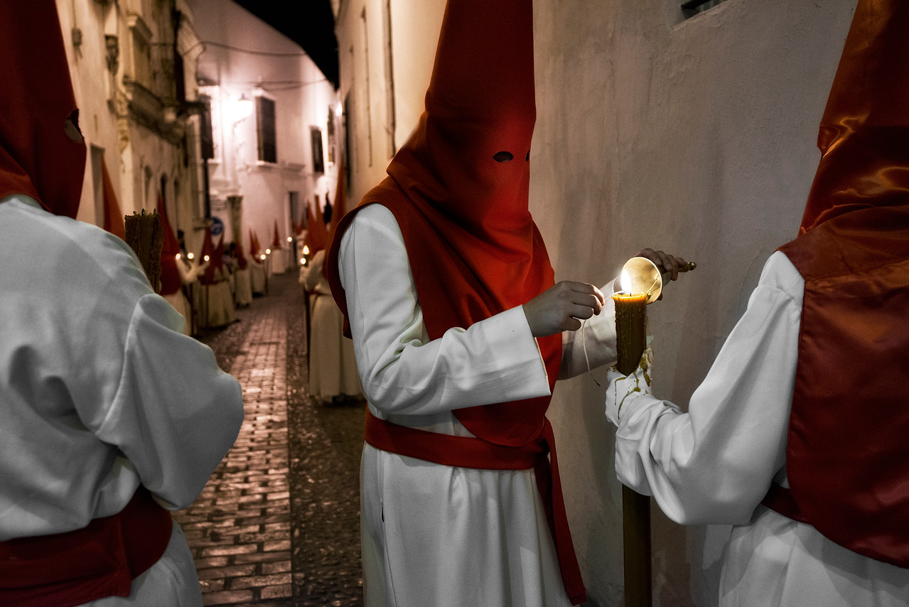 A common feature in Spain's holy week is the almost general usage of the nazareno or penitential robe for some of the participants in the processions. This garment consists in a tunic, a hood with conical tip (capirote) used to conceal the face of the wearer, and sometimes a cloak. The exact colors and forms of these robes depend on the particular procession. The robes were widely used in the medieval period for penitents, who could demonstrate their penance while still masking their identity. These nazarenos carry processional candles or rough-hewn wooden crosses, may walk the city streets barefoot, and, in some places may carry shackles and chains on their feet as penance. In some areas, sections of the participants wear dress freely inspired by the uniforms of the Roman Legion.<br /> <br /> Arcos de la Frontera, Andalucia, Spain, 2014