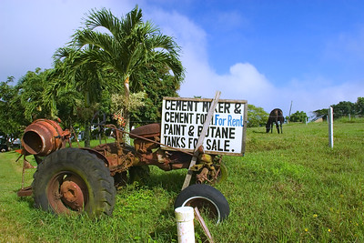 Old tractor with sign to rent cement mixer in Spanish Lookout, Cayo, Belize.