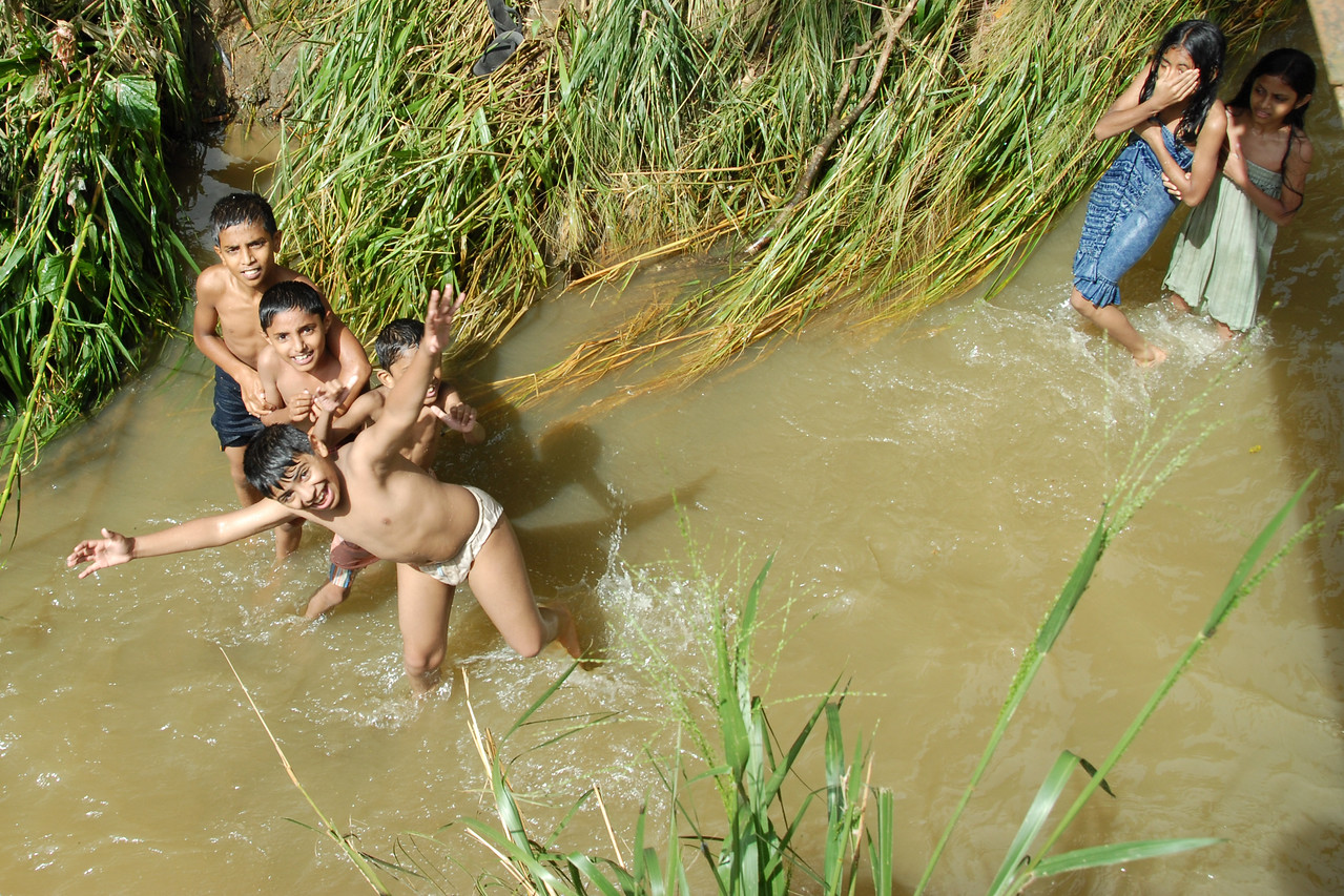 Children in Sri Lanka splashing in water and having fun while taking their bath as well as washing their cloths in a stream passing adjacent to the road. This stream also serves as a waste outlet. Location: Near Colombo, Sri Lanka.