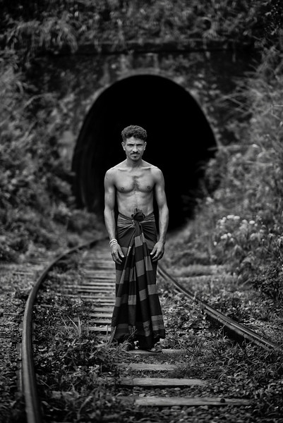 A man stops for a picture on his way to wash at a near by river. It is common for locals to use the train tracks as walking paths between villages. The trains are so noisy and slow that they pose a minimum threat.<br /> <br /> Sri Lanka, 2014.