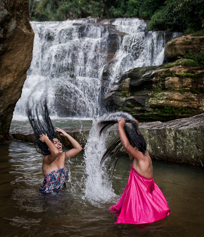Vasena (18) and Akila (11) from the town of Palogole are  playing while washing there hair in a water fall near the mountain town of Nuwara Eliya.<br /> <br /> Sri Lanka, 2014.