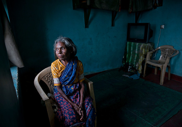 The tea plantation is structured in a social hierarchy. The women, who make up 75%–85% of the work force in the tea industry, are at the lowest social strata and are powerless. This is not unusual as the subordinance of women under men is present domestically and in the social community in many parts of Sri Lanka.   Wages are typically particularly low. In Nuwara Eliya, women were once paid as little as 7 rupees per kilogram, the equivalent of 4 pence, or 7 cents, and many must complete 16 kilograms a day. Given the social stratification in Sri Lanka's past, the pay had to be collected by a husband or father. The men who work on the tea plantations typically cut down trees or operate machinery and are better paid at 155 rupees (82p) a day and finish their working day hours earlier. Due to the severely low wages, industrial action took place in 2006. Wages in the tea sector were increaseded to an average daily wage of 378 rupees for men and 261 for women.   However, studies have revealed that poverty is still a major problem and despite the tea industry employing a large number of poor people, employment has failed to alleviate poverty since workers are often highly uneducated and unskilled. Poverty levels on plantations have consistently been higher than the national average, and although overall poverty in Sri Lanka has declined in the last thirty years, it is now significantly concentrated in rural areas.  Life long tea plucker sits by the window of her small home and looks out onto the tea plantation.  Sri Lanka, 2014.