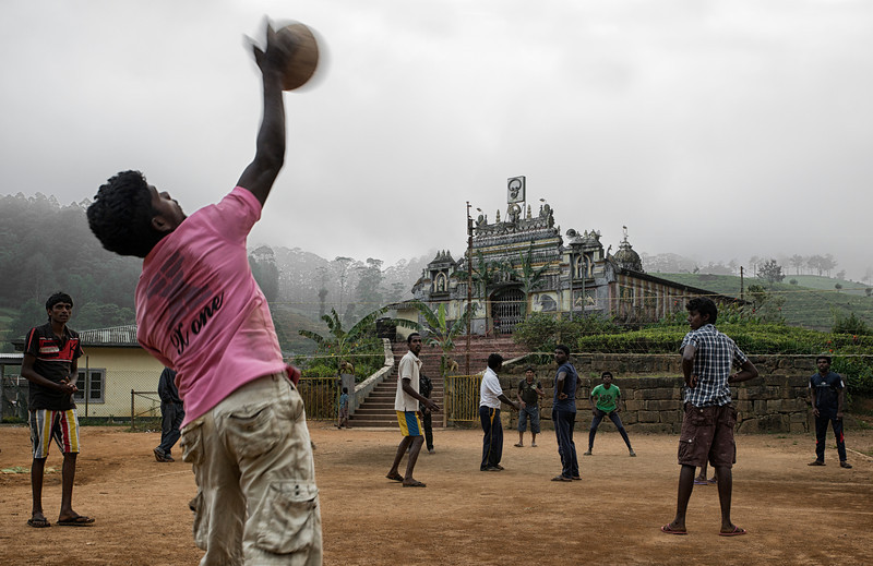Youths playing volleyball at the base of an ancient Hindu temple in a small mountain village.<br /> <br /> Sri Lanka, 2014.