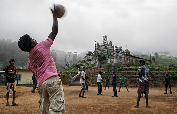 Youths playing volleyball at the base of an ancient Hindu temple in a small mountain village.  Sri Lanka, 2014.
