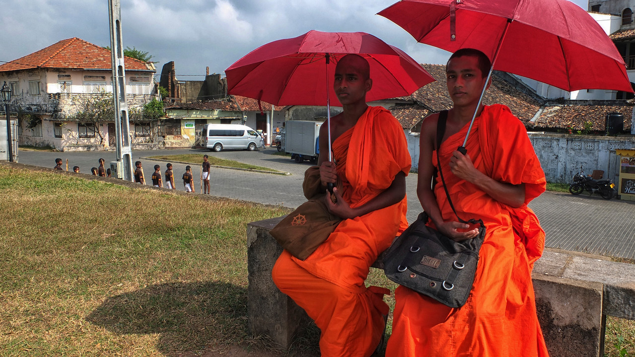 Two Buddhist monks rest on a bench while young military cadets practise drills in the background.<br /> <br /> Galle fort, Sri Lanka, 2014.