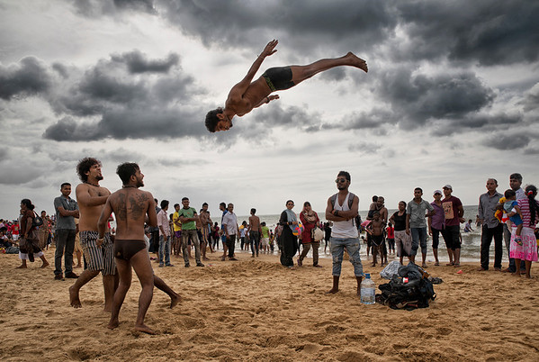 Negombo is a major city in Sri Lanka, located on the west coast of the island at the mouth of the Negombo Lagoon. The beach here gets busy with locals on weekends and public holidays, like in this photo where local youths practice there acrobatic skills during Christmas day.  Negombo, Sri Lanka, 2014.