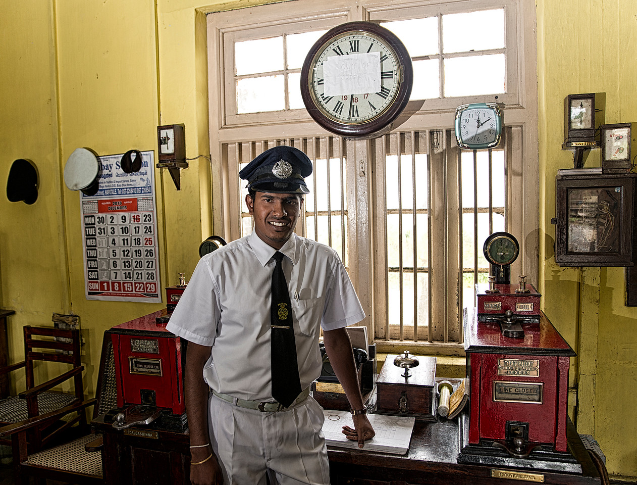 The railway network was introduced by the British colonial government in 1864. The main reason for building a railway system in Sri Lanka (then Ceylon) was to transport tea and coffee from the hill country to Colombo. Initially the service began with the Main Line of 54 kilometres connecting Colombo and Ambepussa. <br /> <br /> Sir Guilford Lindsey Molesworth became the first chief engineer and later Director General of the government railways. During this time, many Sri Lankans referred to the trains as the Anguru Kaka Wathura Bibi Duwana Yakada Yaka (the coal-eating, water-drinking, sprinting, metal devils).Though the British established the railway system, the golden era of Sri Lanka Railways was during 1955–1970 under the management of B.D Rampala, the most respected chief mechanical engineer and later General Manager of CGR. Rampala worked to maintain punctuality and improve comfort. He led the upgrading of major railway stations outside Colombo, and the rebuilding of the track in the Eastern Province to facilitate heavier and faster trains. He launched express trains, many of which were given iconic names. In effect, he ensured that Sri Lanka's railway system was up-to-date in technology and offering greater comfort to its passengers.<br /> <br /> Mr Chander, Station Master at Haputale train station.<br /> Haputale, Sri Lanka, 2014