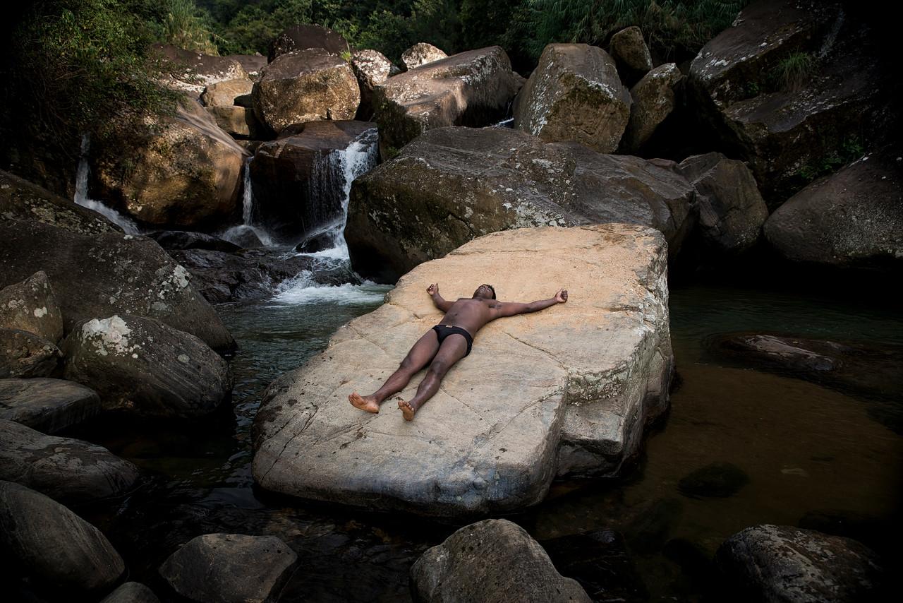 Man enjoying the sun at a waterfall near the mountain town of Nuwara Eliya.<br /> <br /> Sri Lanka, 2014.
