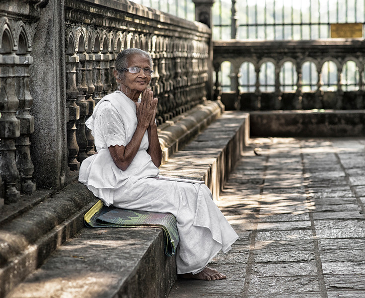 An old lady sits and prays in the Gadaladeniya, Hindu temple grounds.<br /> <br /> Sri lanka, 2014.