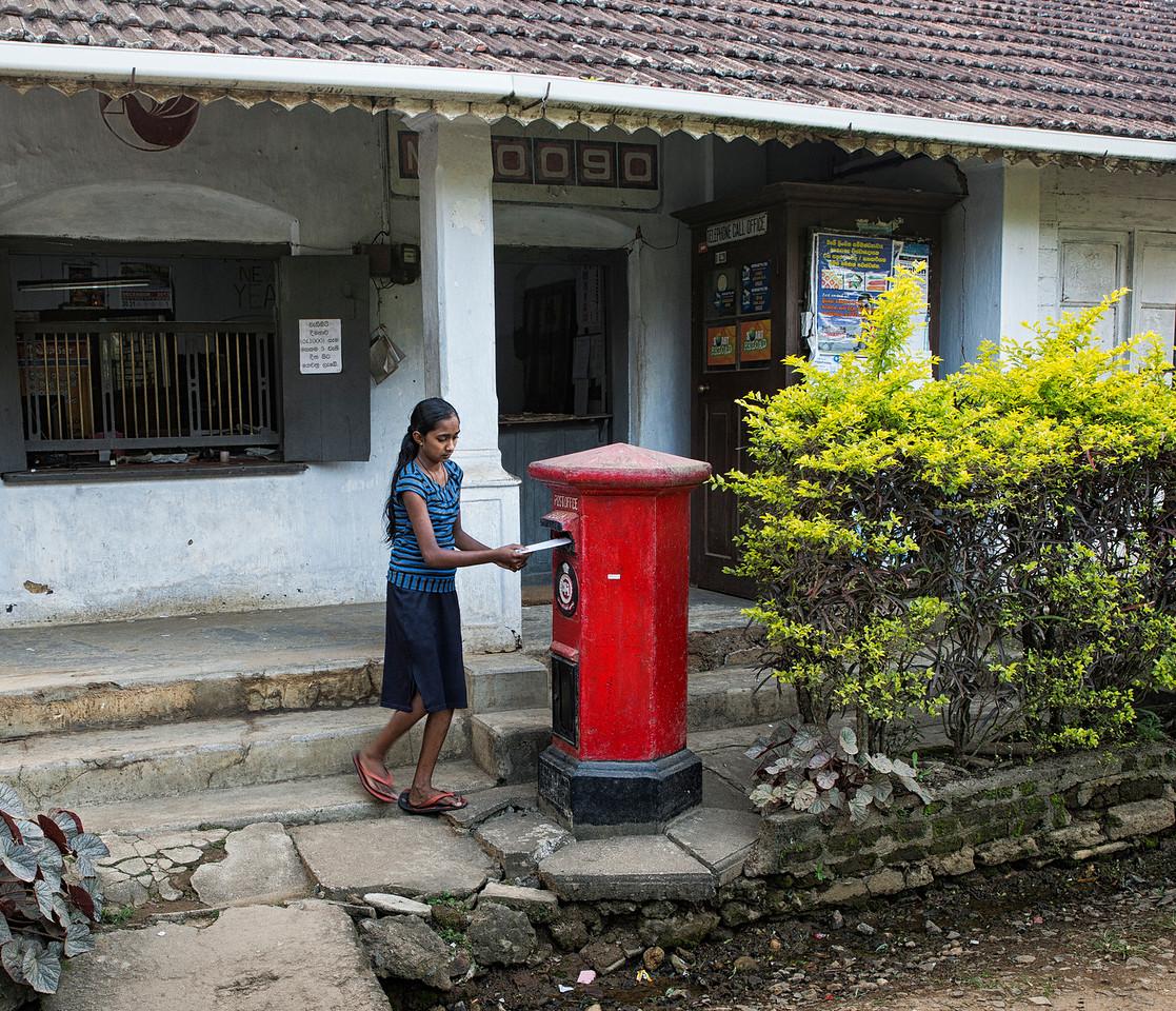 Girl posting a letter at the local post office.<br /> <br /> Ella, Sri Lanka, 2014.