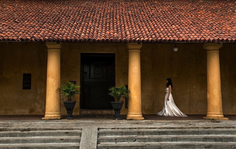 A bride walking past one of the many historical buildings in Galle Fort.<br /> <br /> Sri Lanka, 2014.