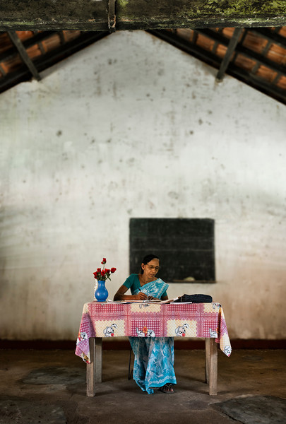 Teacher marking the students' homework in class during the school break.<br /> <br /> Sri Lanka, 2014.