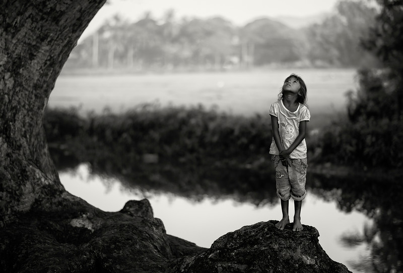 Girl playing by a tree. <br /> <br /> Tissamaharama, Sri Lanka, 2014.