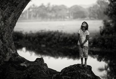 Girl playing by a tree.   Tissamaharama, Sri Lanka, 2014.