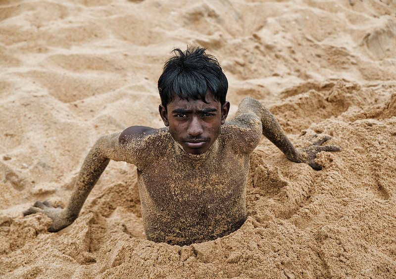 Boy playing at the beach in Negombo.<br /> <br /> Sri Lanka, 2014.