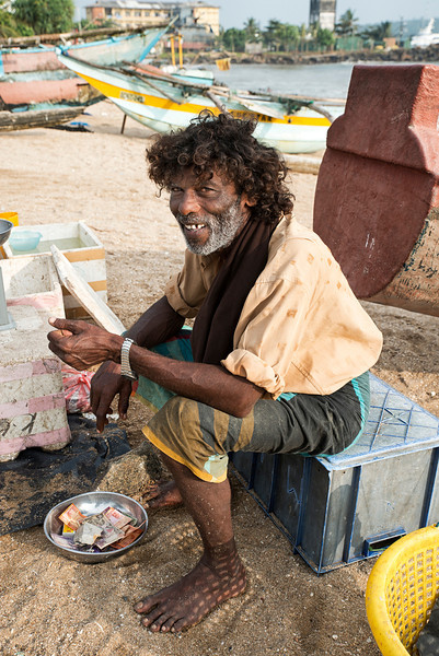Man selling fish on a beach near Galle. <br /> <br /> Sri Lanka, 2014.