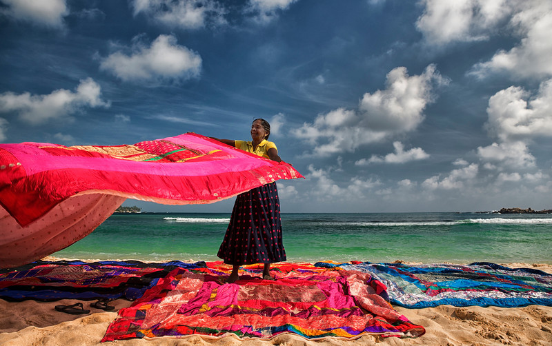 Lady selling colourful fabrics at the beach in Unawatuna. <br /> <br /> Sri Lanka, 2014.