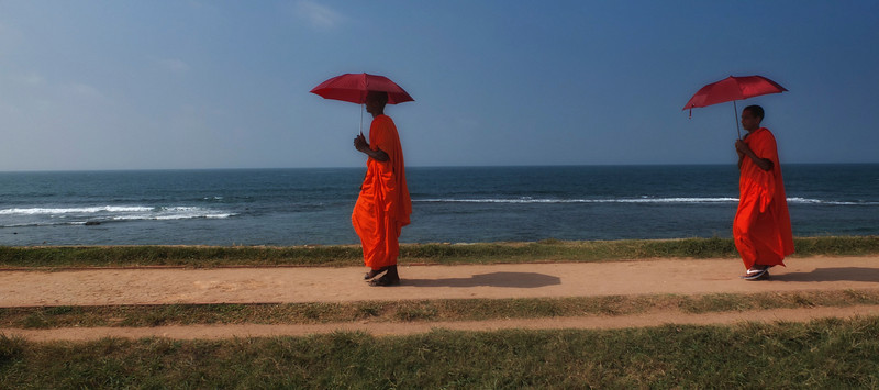 Two Buddhist monks walking along the defensive walls at Galle fort.<br /> <br /> Galle fort, Sri Lanka, 2014.