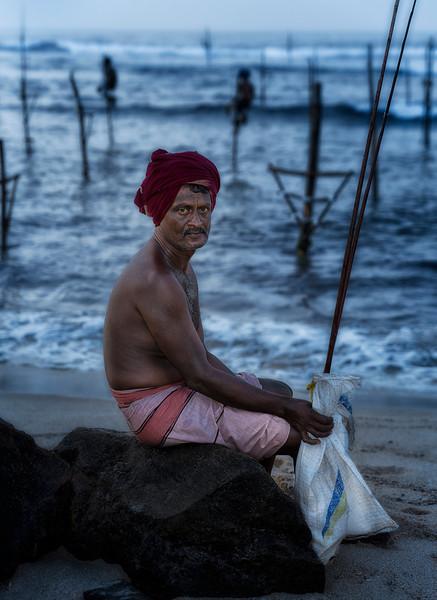 Stilt fisherman takes a rest at the end of a long hard days work.<br /> <br /> Weligama, Sri Lanka, 2014.