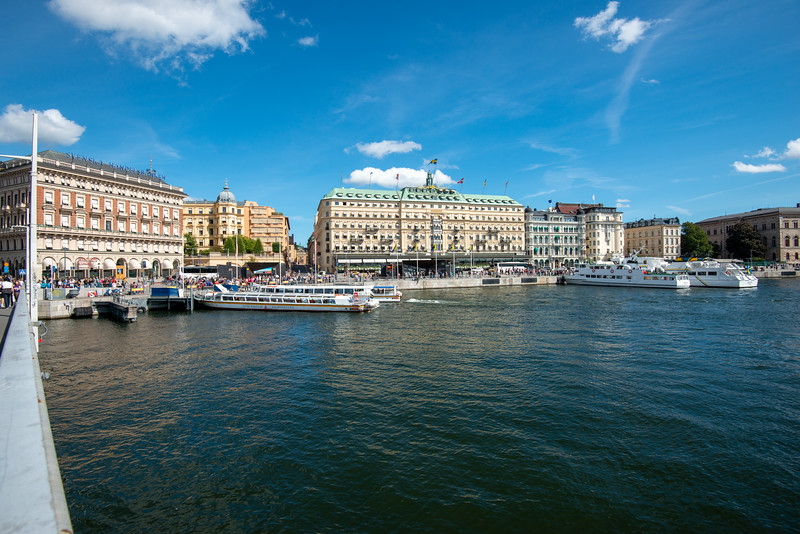 Street view of Stockholm, Logårdstrappan, Skeppsbron, Sweden. In front is Grand Hotel Royal, Stallgatan, Stockholm,  an upscale hotel from 1874, offering water views, dining & an ornate bar, plus a spa & an indoor pool.