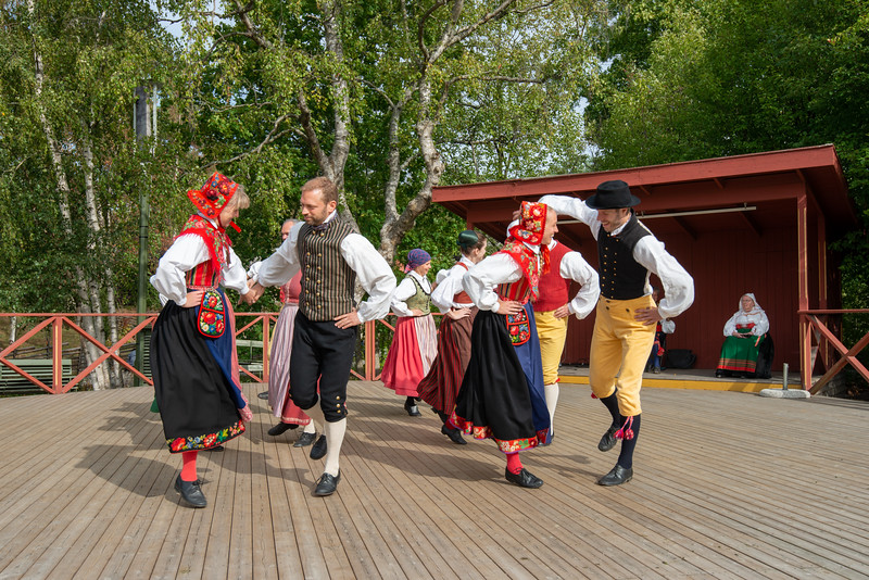 Swedish performers in traditional dresses sing and dance at Skansen, Djurgårdsslätten, Stockholm, Sweden. Is an large open-air Swedish history museum, with buildings, people in costume & a zoo with Nordic animals.