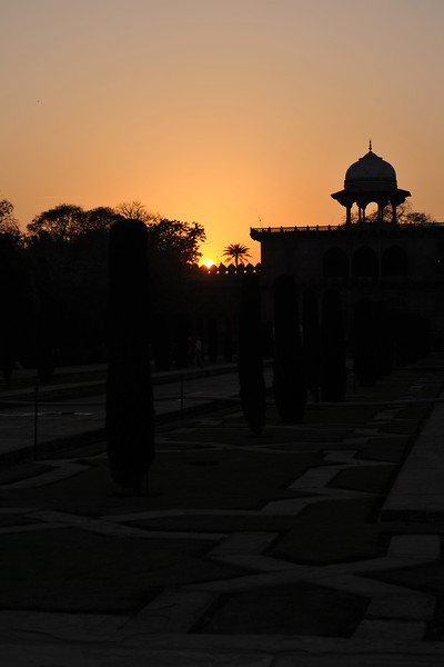 Sunset at Taj Mahal. The Taj Mahal complex is bounded on three sides by crenellated red sandstone walls, with the river-facing side left open. Outside the walls are several additional mausoleums, including those of Shah Jahan's other wives, and a larger tomb for Mumtaz's favorite servant. These structures, composed primarily of red sandstone, are typical of the smaller Mughal tombs of the era.