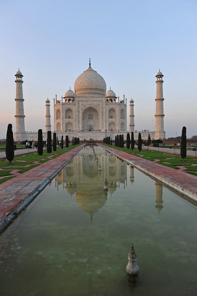 """Taj Mahal, India.<br /> A raised marble water tank at the center of the garden, halfway between the tomb and gateway with a reflecting pool on a north-south axis, reflects the image of the mausoleum. The raised marble water tank is called al Hawd al-Kawthar, in reference to the """"Tank of Abundance"""" promised to Muhammad. The garden uses raised pathways that divide each of the four quarters of the garden into 16 sunken parterres or flowerbeds. Due to its shape, the dome is often called an onion dome or amrud (guava dome). The marble dome that surmounts the tomb is the most spectacular feature."""