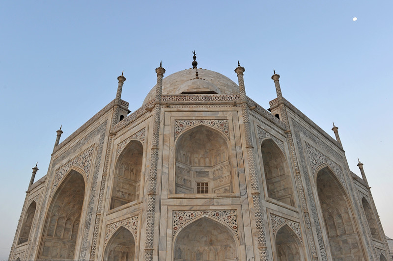 The marble dome that surmounts the Taj Mahal tomb is the most spectacular feature. The top is decorated with a lotus design, which also serves to accentuate its height. The shape of the dome is emphasised by four smaller domed chattris (kiosks) placed at its corners, which replicate the onion shape of the main dome. Their columned bases open through the roof of the tomb and provide light to the interior. The finial is topped by a moon, a typical Islamic motif whose horns point heavenward. Because of its placement on the main spire, the horns of the moon and the finial point combine to create a trident shape, reminiscent of traditional Hindu symbols of Shiva. Tall decorative spires (guldastas) extend from edges of base walls, and provide visual emphasis to the height of the dome. The minarets, which are each more than 40 metres (130 ft) tall, display the designer's penchant for symmetry.