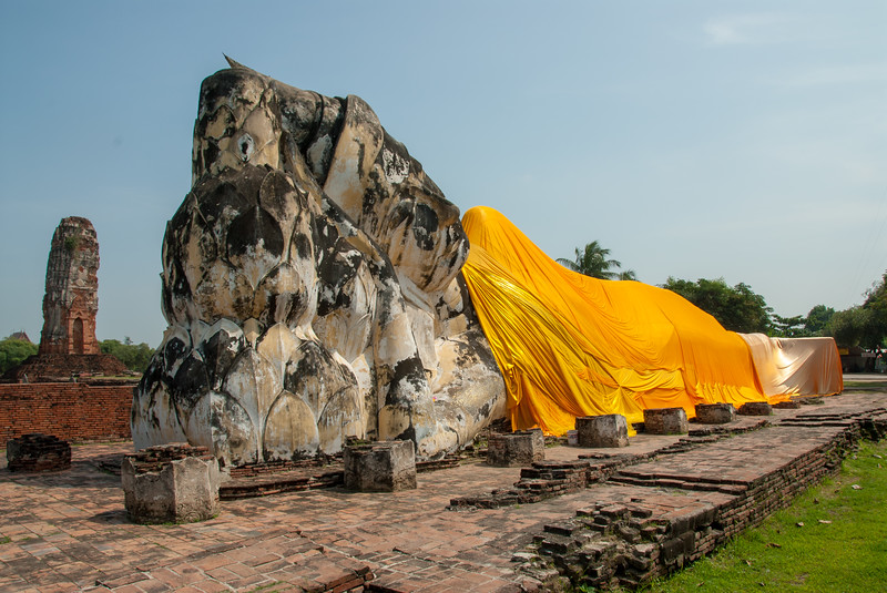Wat Lokkayasutharam, Ayutthaya, Thailand is the location of a large reclining Buddha statue in the open and surrounded by small stupas.