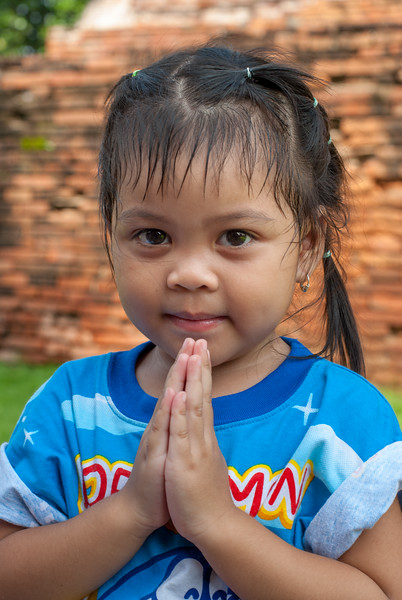 Little buddhist girl doing Namaste. Chai Watthanaram Temple, Ayutthaya, Thailand is a Buddhist temple in the city of Ayutthaya's Historical Park on the west bank of the Chao Phraya River. It is one of Ayutthaya's best known temples and a major tourist attraction. There are restored and not restored ruins of a 17th-century royal Buddhist temple in a picturesque, riverside setting.