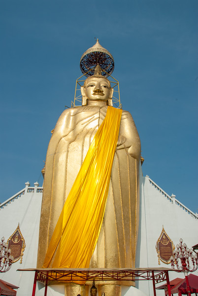 "Golden Buddha statue at Wat Intharawihan (หลวงพ่อโตวัดอินทรวิหาร), Bangkok, Thailand. <br /> <br /> The Wat's main architectural depiction is a 32 metres (105 ft) high, 10 metres (33 ft) wide standing statue referred to as Luang Pho To or ""Phra Si Ariyamettrai"" (Maitreya). Temple dating to the 14th or 15th century, notable for its 32-meter-high gold Buddha statue. or Wat Intharavihan is a wat located in the Phra Nakhon District of Bangkok, Thailand. The temple dating to the 14th or 15th century, is notable for its 32-meter-high gold Buddha statue."
