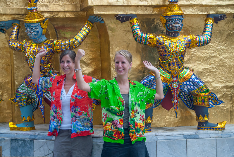 Tourists, especially not from Asia enjoy their visit and experience a new culture & tradition. Grand Palace in Bangkok Thailand with dancing demons holding up roof.
