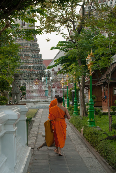 Monks walking at Wat Arun Ratchawararam Ratchawaramahawihan, Bangkok, Thailand.<br /> <br /> Wat Arun Ratchawararam Ratchawaramahawihan or Wat Arun is a Buddhist temple in Bangkok Yai district of Bangkok, Thailand, on the Thonburi west bank of the Chao Phraya River.