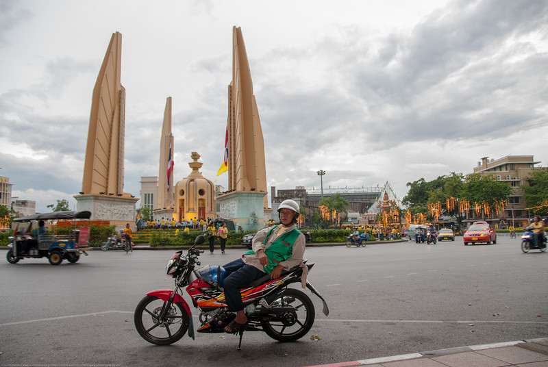 Various modes of transport including bike-taxi. The Democracy Monument is a public monument in the centre of Bangkok, capital of Thailand. It occupies a traffic circle on the wide east-west Ratchadamnoen Avenue, at the intersection of Dinso Road.