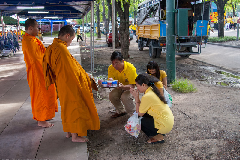 People offer alms and seek blessings of buddhist monks at the celebrations in Bangkok, Thailand.
