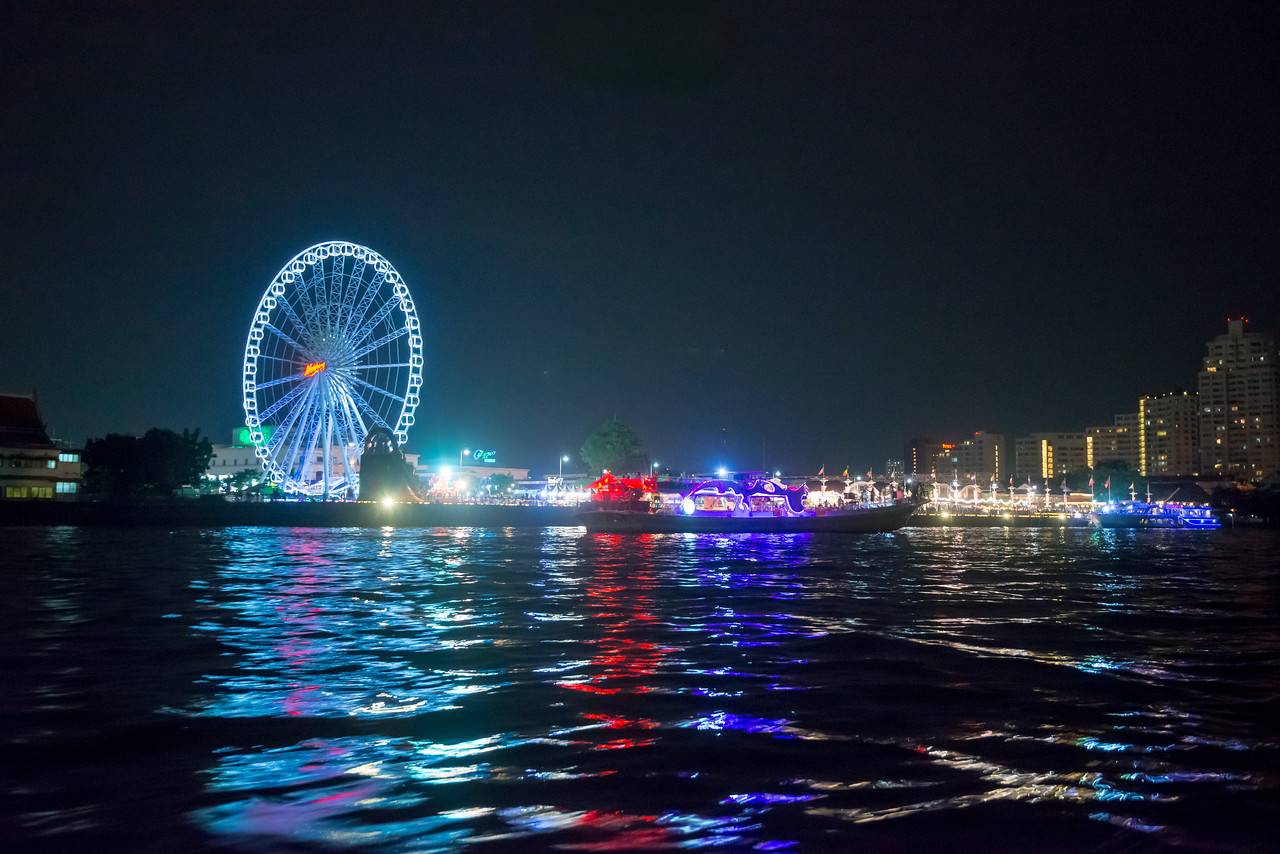 Gaint Ferris Wheel and Bangkok skyline visible at Asiatique The Riverfront, Bangkok, Thailand from the river. This is a large open-air mall and occupies the former docks of the East Asiatic Company. Illuminated at night, it has a sizable Ferris wheel which offers a scenic river views. It opened in April, 2012 and faces the Chao Phraya River and Charoen Krung Road.