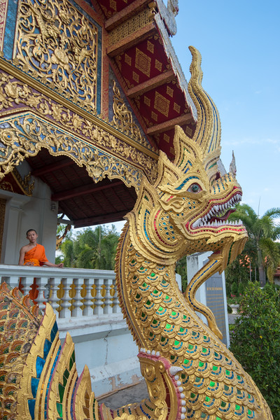 Buddhist monk at the entrance to Wat Phra Singh Woramahawihan (วัดพระสิงห์วรมหาวิหาร ), 14th-century Buddhist temple boasting gold & copper Buddhas, murals & ancient manuscripts. Chiang Mai, Thailand.