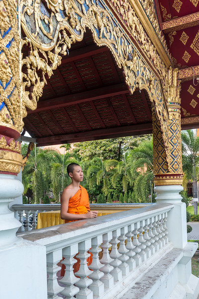 Buddhist monk at the entrance to Wat Phra Singh Woramahawihan (วัดพระสิงห์วรมหาวิหาร ), 14th-century Buddhist temple boasting gold & copper Buddhas, murals & ancient manuscripts. Chiang Mai, Thailand.