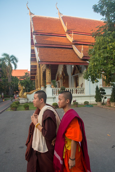 Monks and visitors to Wat Phra Singh Woramahawihan (วัดพระสิงห์วรมหาวิหาร ), 14th-century Buddhist temple boasting gold & copper Buddhas, murals & ancient manuscripts.Chiang Mai, Thailand.