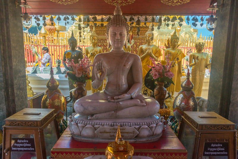 """Buddha statues Wat Phrathat Doi Suthep (วัดพระธาตุดอยสุเทพ), Chiang Mai Province, Thailand. The temple is often referred to as """"Doi Suthep"""" although that is the name of the mountain where it's located. This is a sacred site to many Thai people and is also referred as the ornate temple complex. The complex features a golden stupa, statues & a legendary white elephant shrine."""