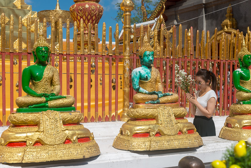 "Buddha statues at Wat Phrathat Doi Suthep (วัดพระธาตุดอยสุเทพ), a Theravada wat in Chiang Mai Province, Thailand. The temple is often referred to as ""Doi Suthep"" although that is the name of the mountain where it's located. This is a sacred site to many Thai people and is also referred as the ornate temple complex. The complex features a golden stupa, statues & a legendary white elephant shrine."