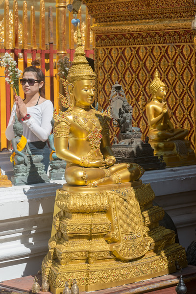 """Buddha statue in gold. Wat Phrathat Doi Suthep (วัดพระธาตุดอยสุเทพ)  is a Theravada wat in Chiang Mai Province, Thailand. The temple is often referred to as """"Doi Suthep"""" although that is the name of the mountain where it's located. This is a sacred site to many Thai people and is also referred as the ornate temple complex. The complex features a golden stupa, statues & a legendary white elephant shrine."""