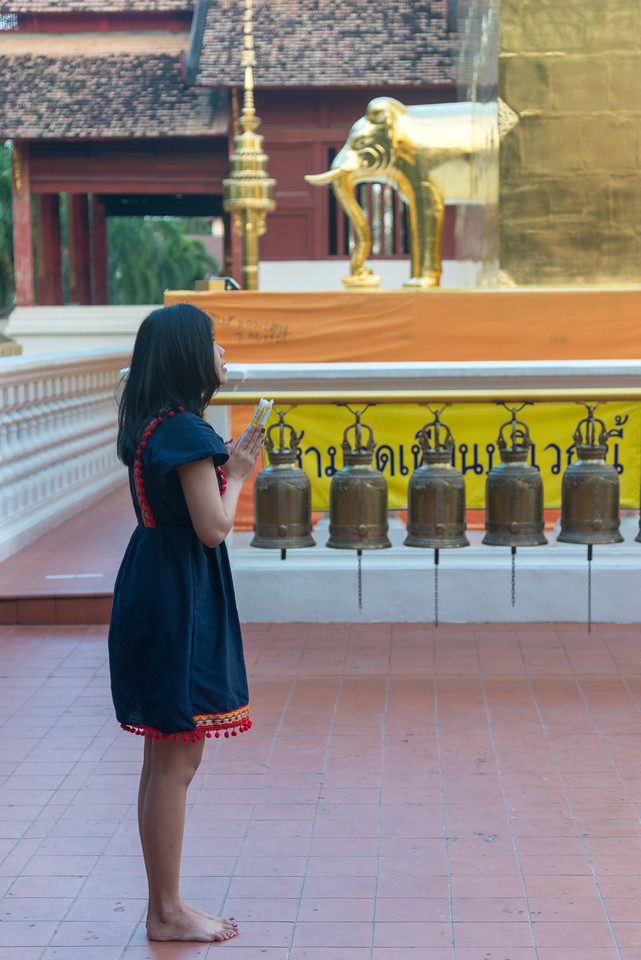 Thai lady offers prayers at Wat Phra Singh Woramahawihan (วัดพระสิงห์วรมหาวิหาร ), 14th-century Buddhist temple boasting gold & copper Buddhas, murals & ancient manuscripts.Chiang Mai, Thailand.