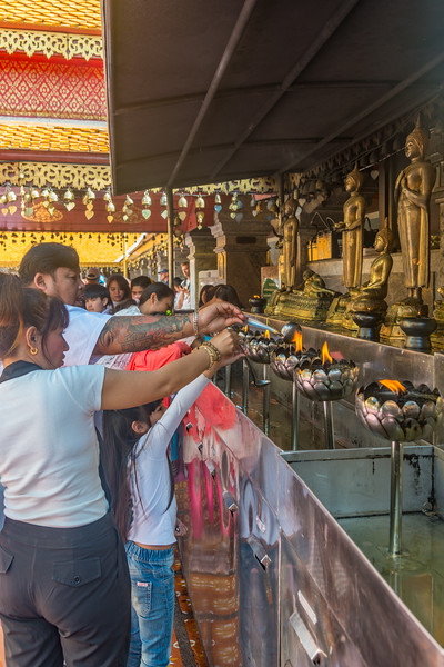 """Buddhists offer prayers at Wat Phrathat Doi Suthep (วัดพระธาตุดอยสุเทพ), a Theravada wat in Chiang Mai Province, Thailand. The temple is often referred to as """"Doi Suthep"""" although that is the name of the mountain where it's located. This is a sacred site to many Thai people and is also referred as the ornate temple complex. The complex features a golden stupa, statues & a legendary white elephant shrine."""