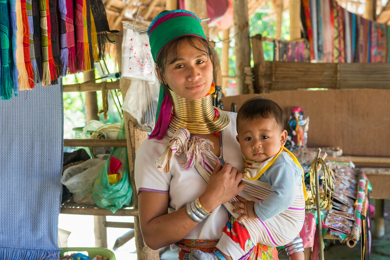 Mother & Child Karen Long Neck. Long Neck Karen in Chiang Rai, Chang Wat Chiang Rai, Thailand<br /> The Karen are a tribal group who have historically lived in the hills on the Myanmar (formerly Burma) side of the Thai border. Best recognized for their elongated necks, the Karen women wear heavy brass rings around their necks, forearms, and shins. There is a lot of criticism surrounding this. From human-zoo to women earning a honest living and not being prosecuted. Depending on which side of the argument you are. When we first arrived each woman was stationed by her own hut busy working on the knitting looms and it initially felt a little bit like a staged atmosphere but talk and spend time and it feels not very different than other villages. Controversy or not, had mixed feelings on this.