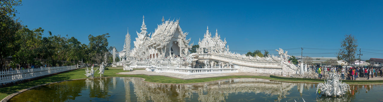Panoramic view of Wat Rong Khun White Temple (วัดร่องขุ่น) <br /> Contemporary Buddhist temple drawing massive crowds with its unique, intricate white exterior. Wat Rong Khun, also known as the White Temple, is a contemporary, unconventional, privately-owned art exhibit in the style of a Buddhist temple in Chiang Rai Province, Thailand.