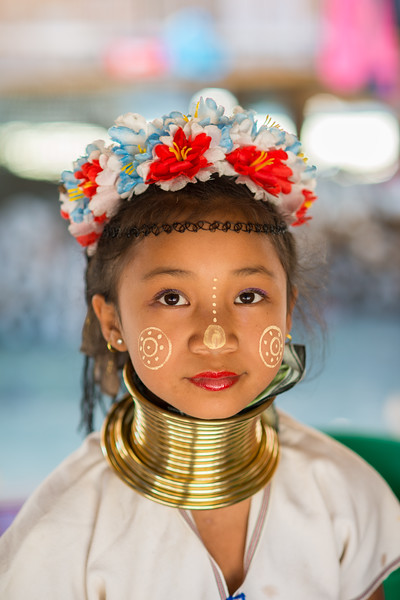 Karen Long Neck girl's portrait. Long Neck Karen in Chiang Rai, Chang Wat Chiang Rai, Thailand<br /> The Karen are a tribal group who have historically lived in the hills on the Myanmar (formerly Burma) side of the Thai border. Best recognized for their elongated necks, the Karen women wear heavy brass rings around their necks, forearms, and shins. There is a lot of criticism surrounding this. From human-zoo to women earning a honest living and not being prosecuted. Depending on which side of the argument you are. When we first arrived each woman was stationed by her own hut busy working on the knitting looms and it initially felt a little bit like a staged atmosphere but talk and spend time and it feels not very different than other villages. Controversy or not, had mixed feelings on this.